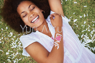 Laughing African American female with a love written on her arm lying on grass