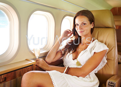 Portrait of a beautiful girl enjoying a glass of champagne in the cabin of a private jet