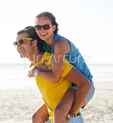 Young girl being piggybacked by her boyfriend at the beach on holiday