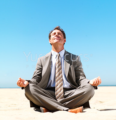 Business man sitting in lotus position meditating on the beach in bright sunshine - copyspace