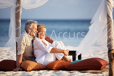 Portrait of relaxed mature couple on a vacation sitting at the beach