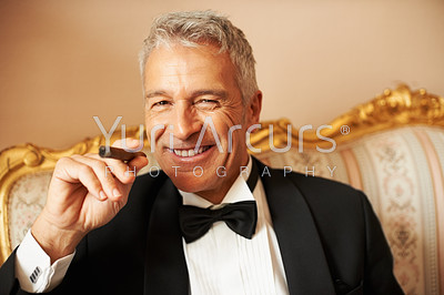 Closeup of classy gentleman smiling handsomely while smoking a cigar on a piece of antique furniture