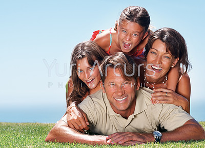 Family of four enjoying outdoors with man lying on grass and family on top of him - copyspace