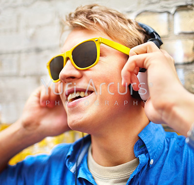 Trendy young guy wearing bright yellow sunglasses listening to music on his headphones