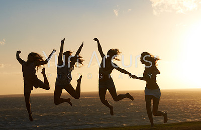 Silhouette of a group of girlfriends on the beach having lots of fun jumping around