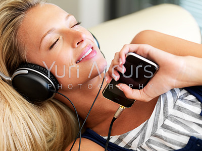 Happy young lady listening to music from her mp3 player