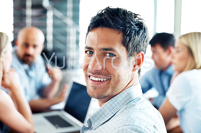 Handsome businessman smiling back at the camera, with an office meeting in progress in the background