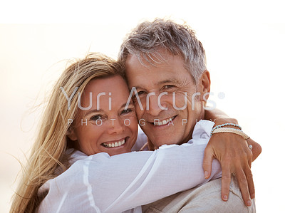 Closeup portrait of a romantic mature couple smiling at you while embracing lovingly