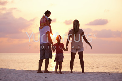 Rear view of loving family enjoying sunset on the beach