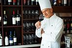 Handsome cook tasting red wine