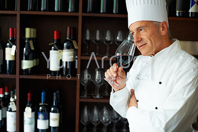 Portrait of smart male chef tasting red wine