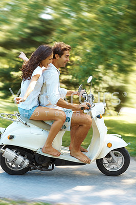 Beautiful young love couple enjoying themselves while riding their scooter in a park - copyspace