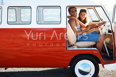 Portrait of young loving couple sitting in their mini van on a road trip - copyspace