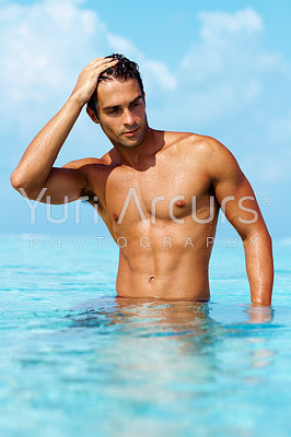 Torso of a gorgeous guy standing in waist deep water looking away thoughtfully with brilliant blue water and sky - copyspace