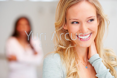 Closeup of a beautiful young woman smiling and looking away, with a blurred image of a woman in the background