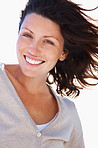 Cute young woman smiling with her hair being blown by wind