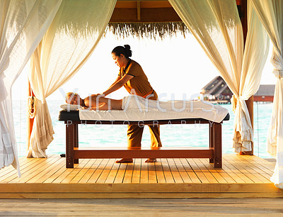 Middle aged Caucasian woman receiving body massage from skilled therapist at spa resort