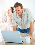 Mature man using laptop while woman on the phone in background