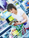 Happy young woman with her purchased grocery items in a cart