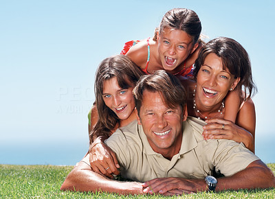 Buy stock photo Family of four enjoying outdoors with man lying on grass and family on top of him - copyspace