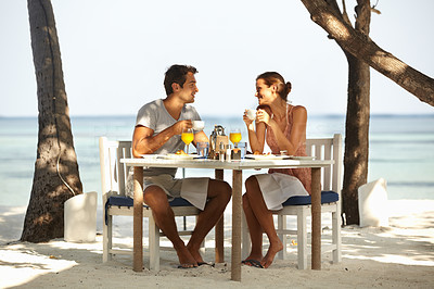 Buy stock photo Young couple having lunch on a tropical beach in front of the ocean