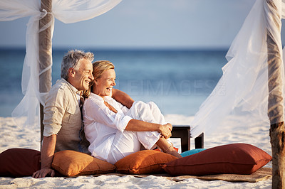 Buy stock photo Portrait of relaxed mature couple on a vacation sitting at the beach