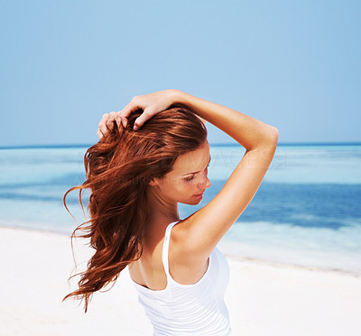Buy stock photo Shot of a beautiful young woman enjoying her beach holiday