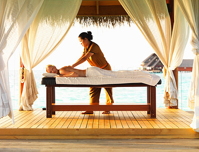 Buy stock photo Middle aged Caucasian woman receiving body massage from skilled therapist at spa resort