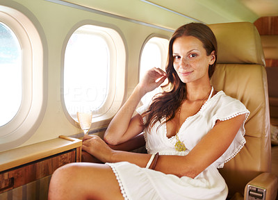 Buy stock photo Portrait of a beautiful girl enjoying a glass of champagne in the cabin of a private jet