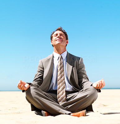 Buy stock photo Business man sitting in lotus position meditating on the beach in bright sunshine - copyspace