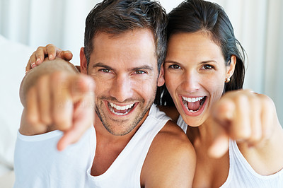 Buy stock photo Portrait of happy couple pointing and laughing together