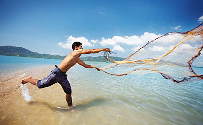 Buy stock photo Shot of a traditional thai fisherman standing in the water casting a net into the ocean
