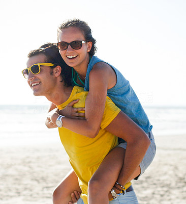 Buy stock photo Young girl being piggybacked by her boyfriend at the beach on holiday