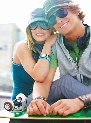 Buy stock photo Portrait of a happy young couple sitting together with skateboard