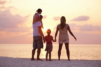 Buy stock photo Rear view of loving family enjoying sunset on the beach