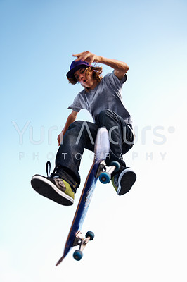 A teenage boy doing a trick on his skateboard