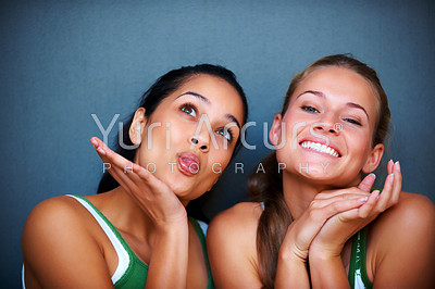 Portrait of pretty young girls making funny faces against grey background