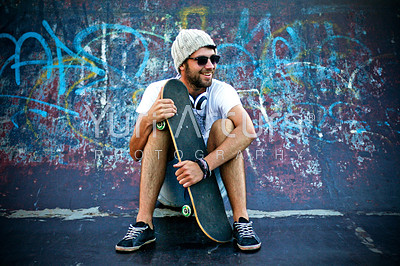 Skateborder sitting in front of a graffitied wall holding his skateboard