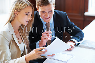 Portrait of happy business executives discussing about document at office