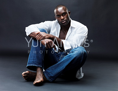 Portrait of an afroamerican young man siiting relaxed on floor against grunge background