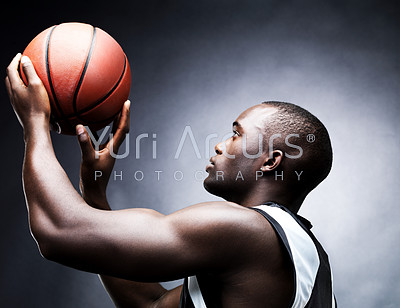 Portrait of a healthy young male basketball player in free throw pose against grunge background