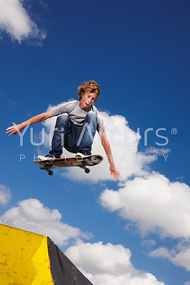 A teenager jumps a ramp on his skateboard - Copyspace