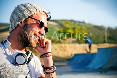 Trendy skater talks to his mates on the phone in a skate park one late afternoon - copyspace