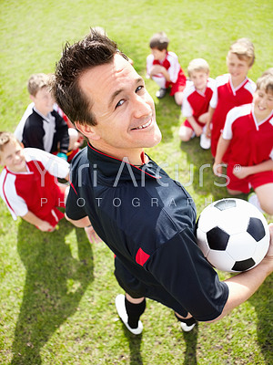 Rear-view portrait of a soccer coach holding a ball with his team in the background