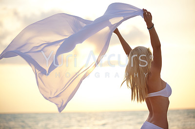 Young woman in bikini at the beach blowing a sarong in a breeze with a pale sunset in the background