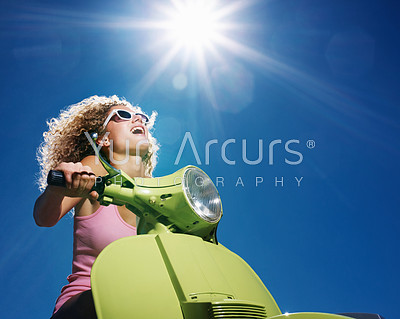 Closeup portrait of young woman with curly hair riding a scooter on a sunny day - Outdoor