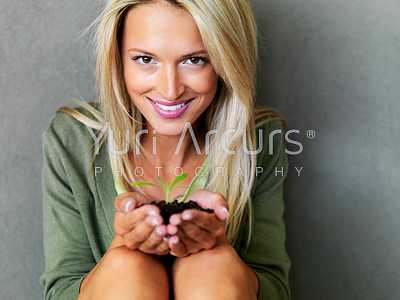 Portrait of a beautiful happy young woman holding a small plant