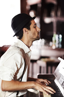 Buy stock photo A handsome young man playing the piano in a club