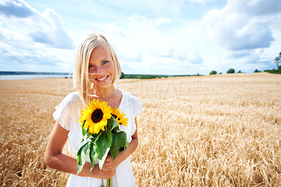 Buy stock photo Positive young woman standing in a wheat field and holding some sunflowers