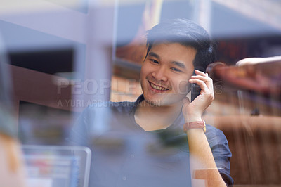 Buy stock photo Smiling Asian man using a mobile phone indoors